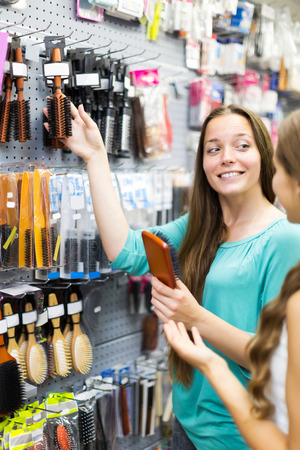 Young girl chooses hairbrush in hardware store