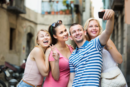 Four cheerful smiling friends taking self portrait with mobile phone in town Stock Photo