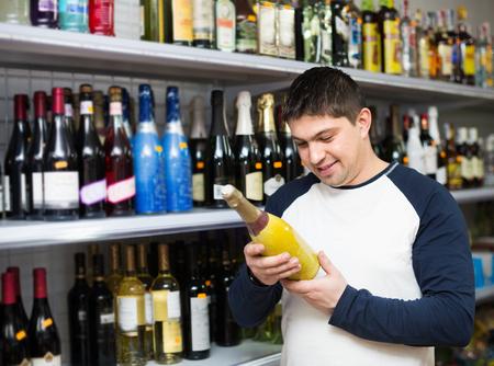 middle class: hombre de clase media de comprar una botella de vino en la tienda de alimentos