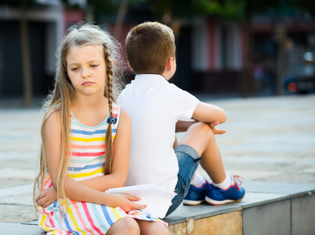 sad girl in preschool age having problem with friend outdoors in park