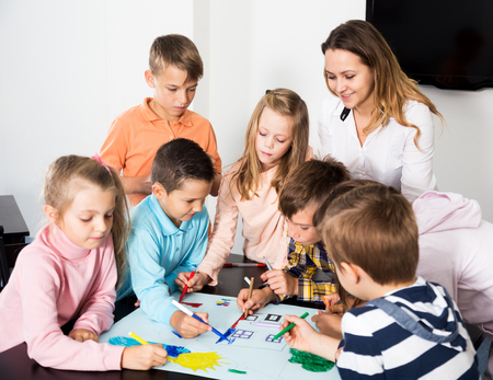 nine year old: Happy team of elementary age children and female teacher drawing on one sheet
