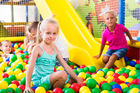 smiling little girl in dress playing on playground with plastic balls with other kids