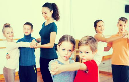 normal school: Group of caucasian children dancing tango in dance studio