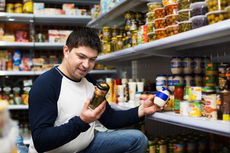 clase media: chico de clase media ordinaria compra de alimentos enlatados en el supermercado Foto de archivo