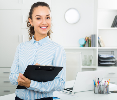 Portrait of successful business lady holding pad documents in hands in office Stock Photo