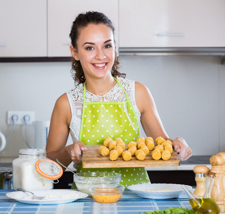 domestic kitchen: Happy housewife cooking breadcrumbed croquettes in domestic kitchen