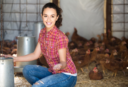 happy young european woman farmer holding bucket with chicken forage in hen house