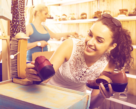 desires 25: Positive girl choosing a pair of shoes while other customer still  looking Stock Photo