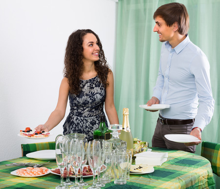 Young couple serving table for dinner at home
