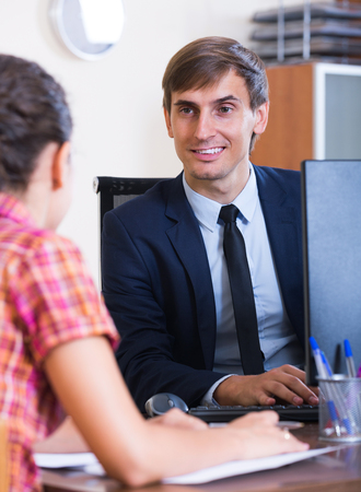 Banking smiling american agent with nice offer consulting customer indoors Stock Photo
