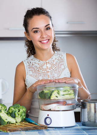 domestic kitchen: Happy smiling housewife steaming salmon and vegetables in domestic kitchen