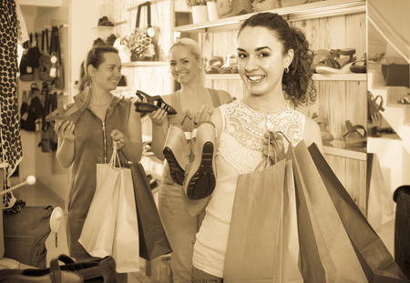 desires 25: three happy girls holding a paper shopping bags in the boutique