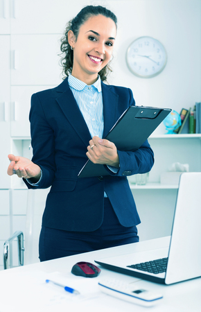 Portrait of happy smiling positive businesswoman with clip pad in modern office