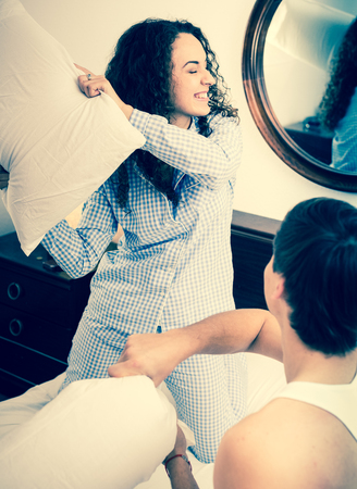 young wife: Laughing husband and young brunette wife having pillow fight