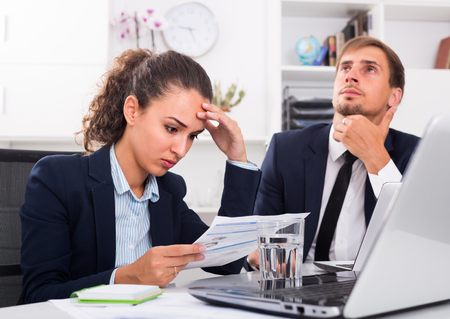 solve problems: portrait of worried business man and woman colleagues trying to solve problems in office . Focus on woman Stock Photo