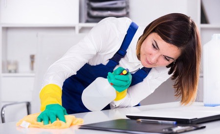 serviceable: Smiling woman cleaner working effectively on task in office