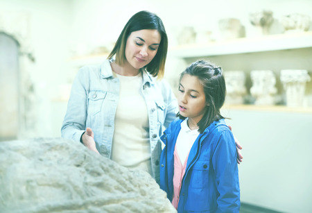 Young mother and daughter exploring old bas-reliefs in museum. Focus on child