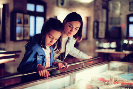 Attractive mother and daughter exploring expositions of previous centuries in museum. Focus on the woman 스톡 콘텐츠