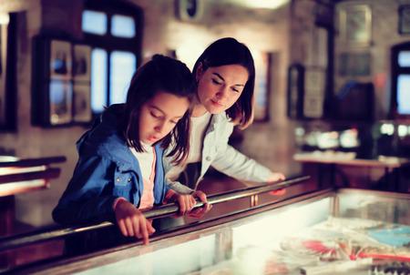 Madre e figlia attraenti che esplorano le esposizioni dei secoli precedenti in museo. Concentrati sulla donna
