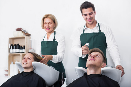 18's: Portrait customers and hairstylers washing hair in salon