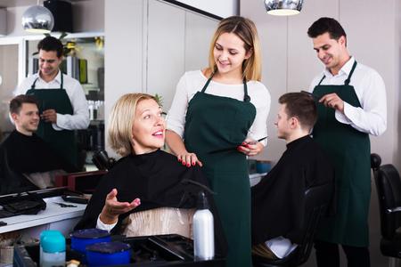 esthetics: Friendly blonde cuts hair of mature woman at salon