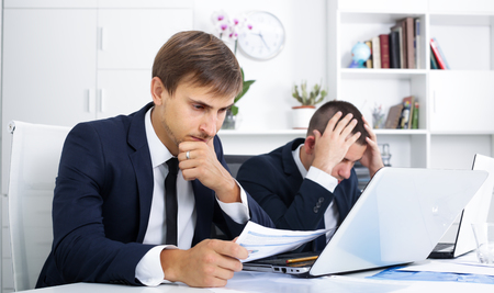 business failure: Two sad young males coworkers experiencing business failure in firm office Stock Photo
