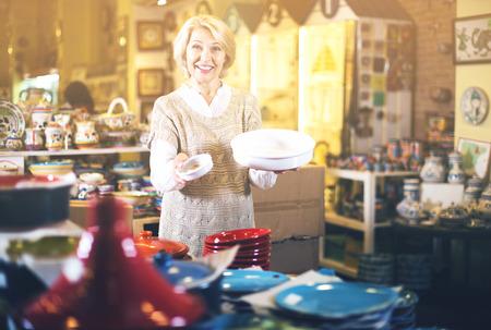 cookware: Mujer madura seleccionar la vajilla de cerámica en la tienda de utensilios de cocina Foto de archivo