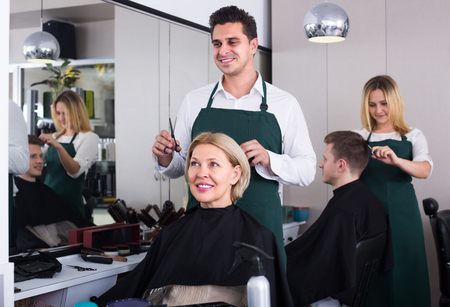 18's: Smiling dark-haired man doing hairstyle for mature blonde woman in hairdressing saloon. Selective focus on woman