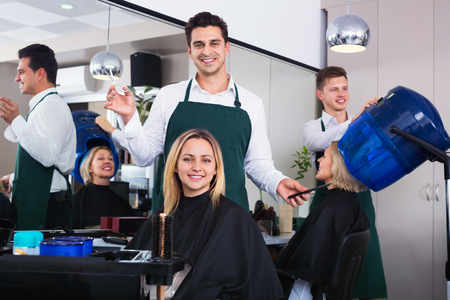 18's: Cheerful  positive man cutting long hair of girl in hairdressing saloon Stock Photo