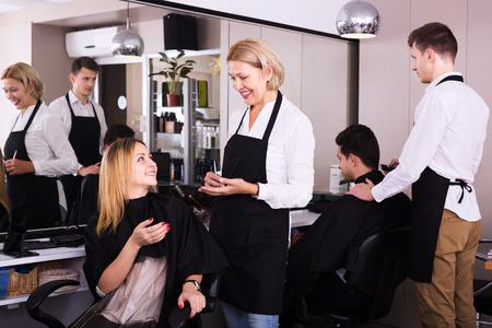 19's: Elderly woman cuts hair of blonde girl in barbershop. Focus on hairdresser