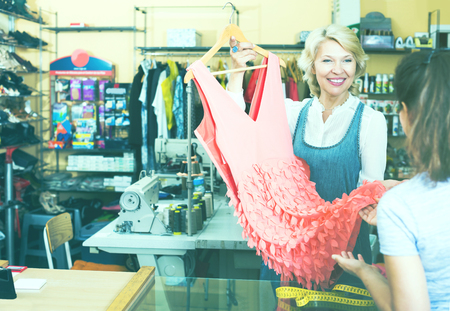 customer tailor: Smiling mature employee returning dress to customer in sewing studio Stock Photo