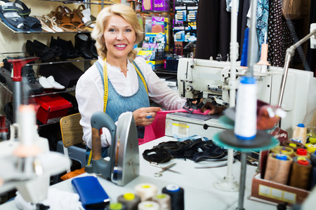 Professional elderly blonde woman tailor working on sewing machine at studio