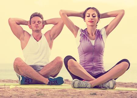 crosslegged: Cross-legged young american couple practice yoga on beach in morning Stock Photo