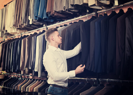 acquiring: positive male customer examining suits in men's cloths store