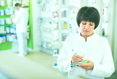 diligent: Portrait of diligent  friendly glad female druggist in white coat working in pharmacy