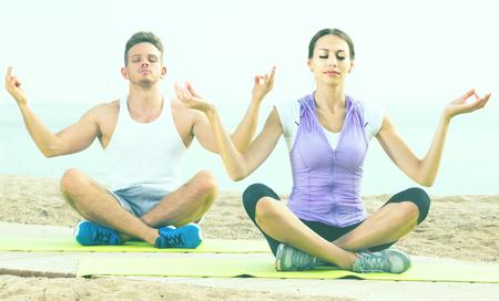 crosslegged: Cross-legged adult spanish couple practice yoga on beach in morning Stock Photo