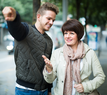 met: Glad man points the direction to woman outdoor Stock Photo