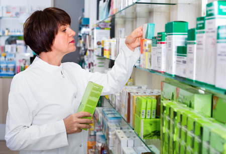 diligente: Portrait of diligent smiling glad female druggist in white coat working in pharmacy