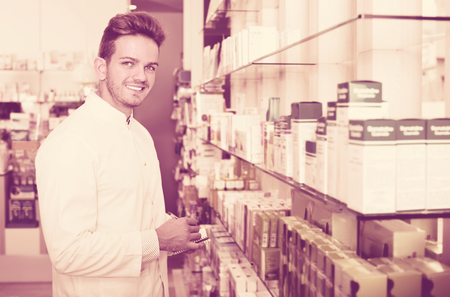 buying questions: Smiling positive cheerful male pharmacist wearing white coat standing among shelves in drug store