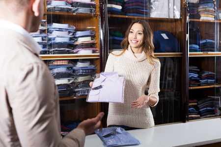 seller: Glad female seller demonstrating shirts in men�s clothes store