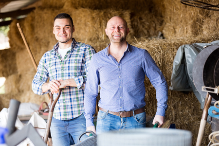 hayrick: Two nice farm workers tedding the hay at hayloft. Focus on the right man