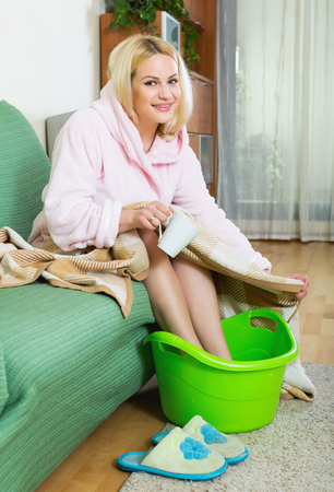 footcare: Smiling young woman in bathrobe sitting with feet in basin