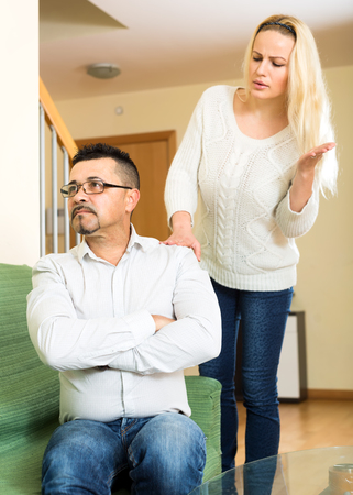 nagging: Wife is nagging her husband in a living room