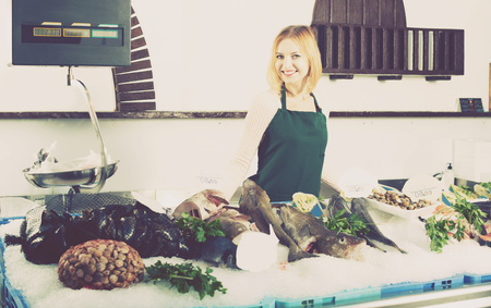 fish selling: Young female shop assistant selling fresh fish and chilled seafood