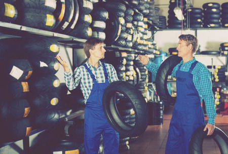 polite: Two polite colleagues working with motorcycle tires in service point