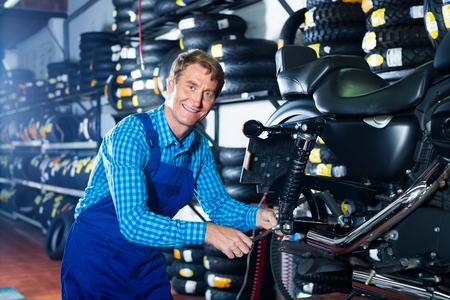 joyful smiling mature professional mechanic man examining motorcycle in shop