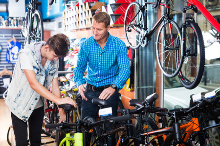 family units: Adult father with young teenager boy trying new racing bicycle in sport shop