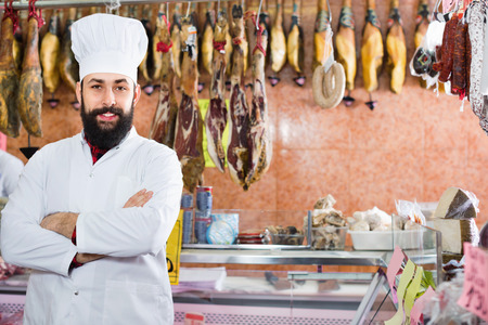 sorts: Cheerful  man seller showing sorts of meat in butcher�s shop Stock Photo