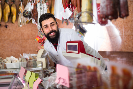 sorts: Male shop assistant demonstrating sorts of fresh meat in butcher�s shop