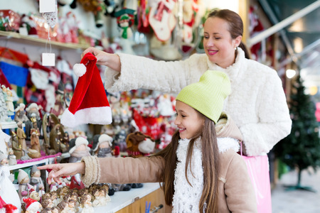 5s: Smiling mother with happy small daughte buying decorations for Xmas. Focus on girl